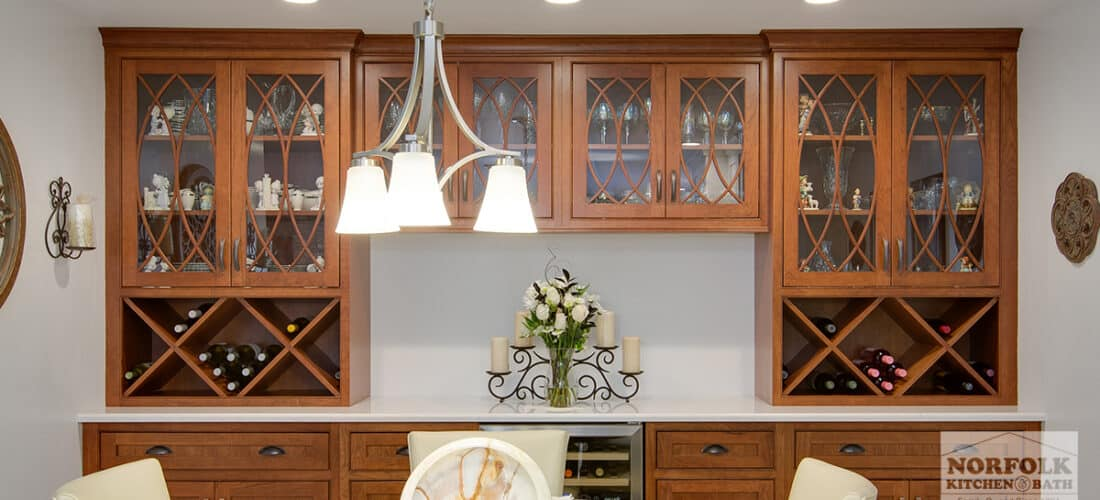 a dining hutch area in a medium wood finish with gothic mullion glass doors and 2 wine racks underneath