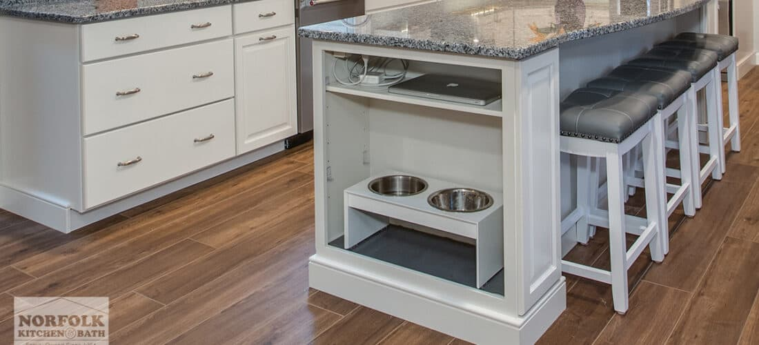 a white kitchen island with 4 stools and a bookshelf on the end with two shelves: one with a laptop and charger on it and another with a double dog bowl on it.