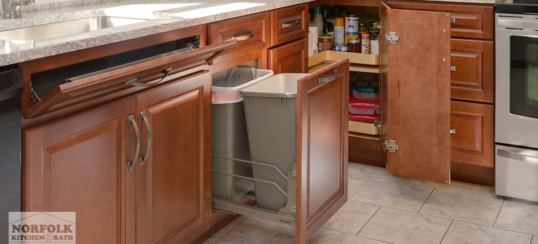 a cherry kitchen with multiple cabinet upgrades: a tilt out tray, double pull out trash and a lazy susan