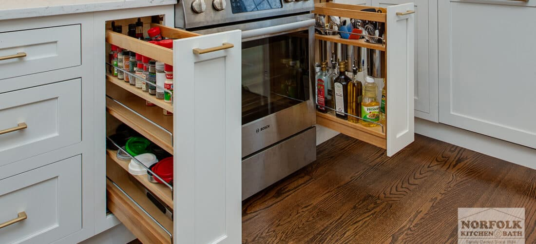 a white kitchen with 2 pull out spice racks on either side of the oven