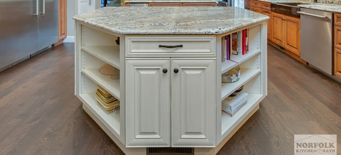 a hexagon shaped white island with a double door cabinet in front and two 3-tier bookshelves on either side