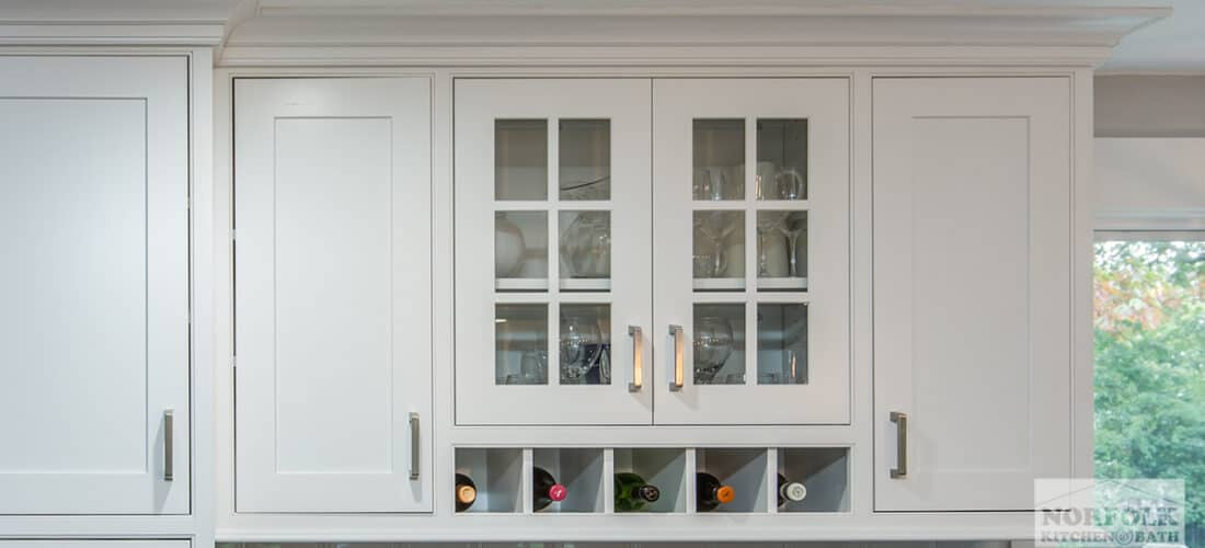 decorative glass mullion kitchen cabinet doors with a small wine rack underneath