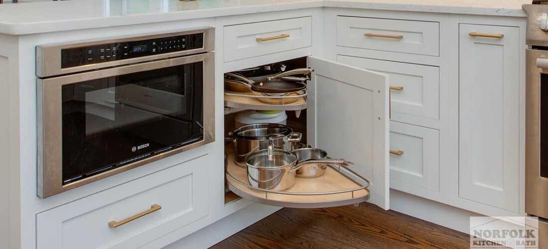 a white kitchen with an open cabinet door with a blind corner cabinet upgrade filled with pots and pans