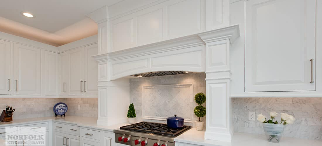 a large white decorative range hood hanging over a 6 burner gas cooktop in an all white kitchen design