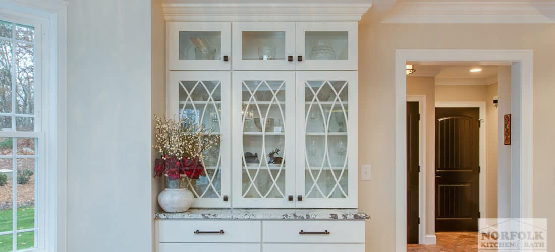 white hutch cabinetry with decorative gothic mullion glass doors