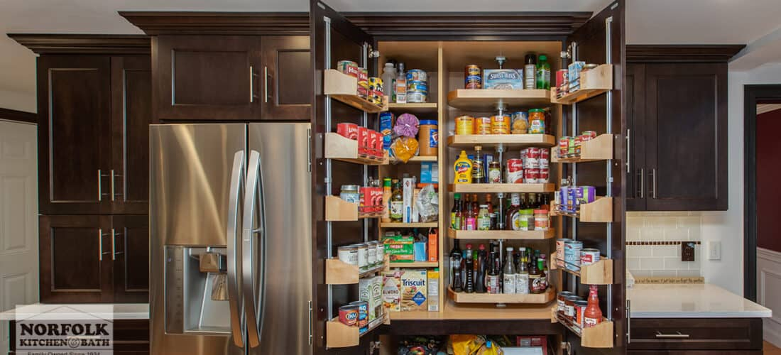 a huge pantry cabinet in a dark wood finish with a variety of shelving options