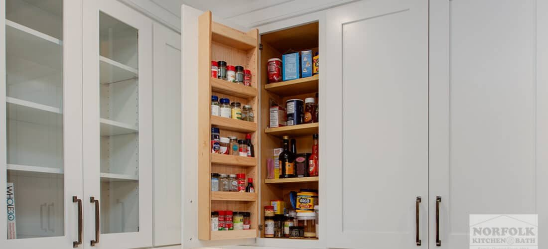 a wall kitchen cabinet that is open to reveal a specialty spice shelf on the inside of the cabinet door