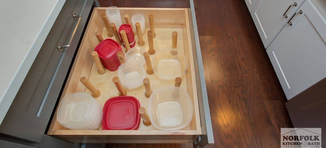 a large kitchen drawer with peg storage for tupperware