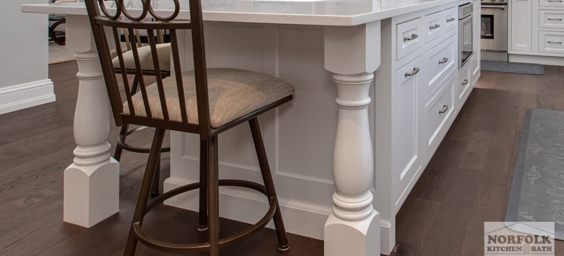 a large white kitchen island with one bar stool and decorative furniture posts on either side