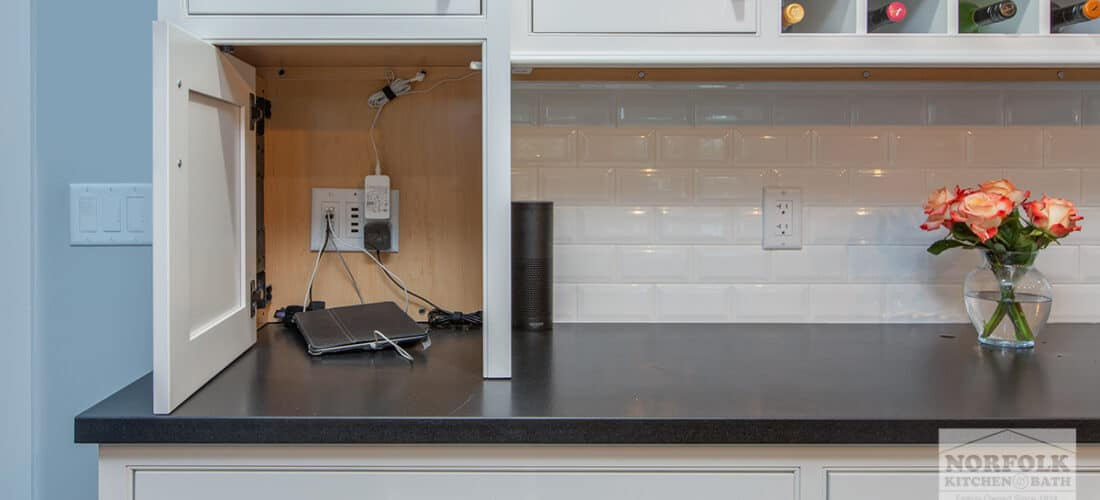 a wall kitchen cabinet that is used to hide small electronics while they are charging