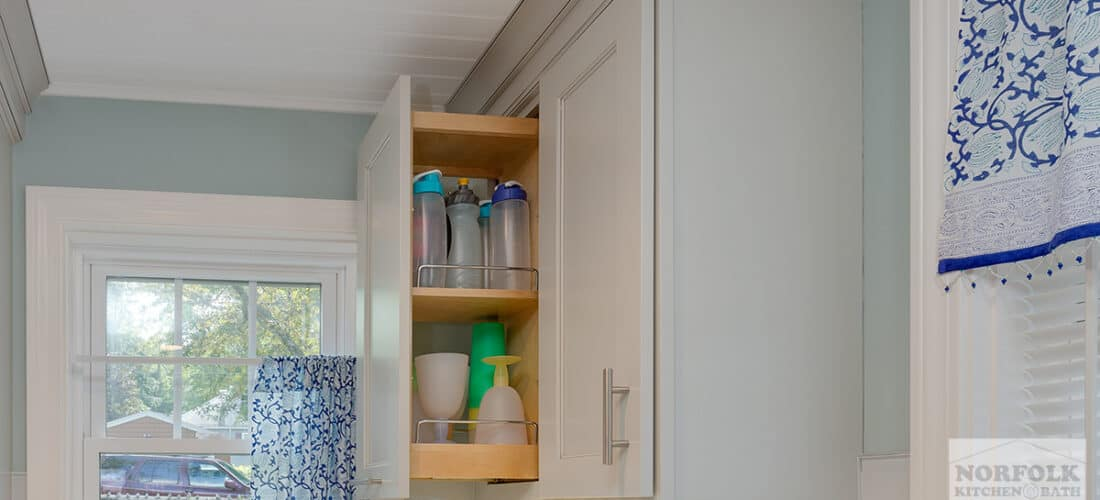 a wall kitchen cabinet with a pull out upgrade that is holding different types of cups