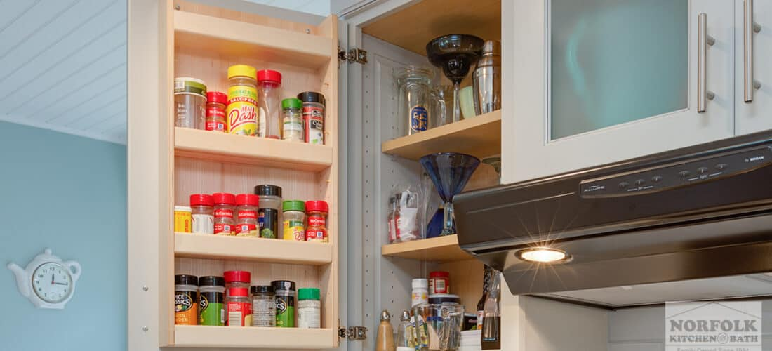 a wall kitchen cabinet with an open door showing a spice rack upgrade with spices on it