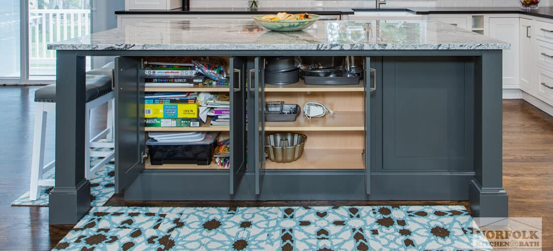 a gray island in a white kitchen with 2 open cabinets that reveal storage shelving underneath the island seating area