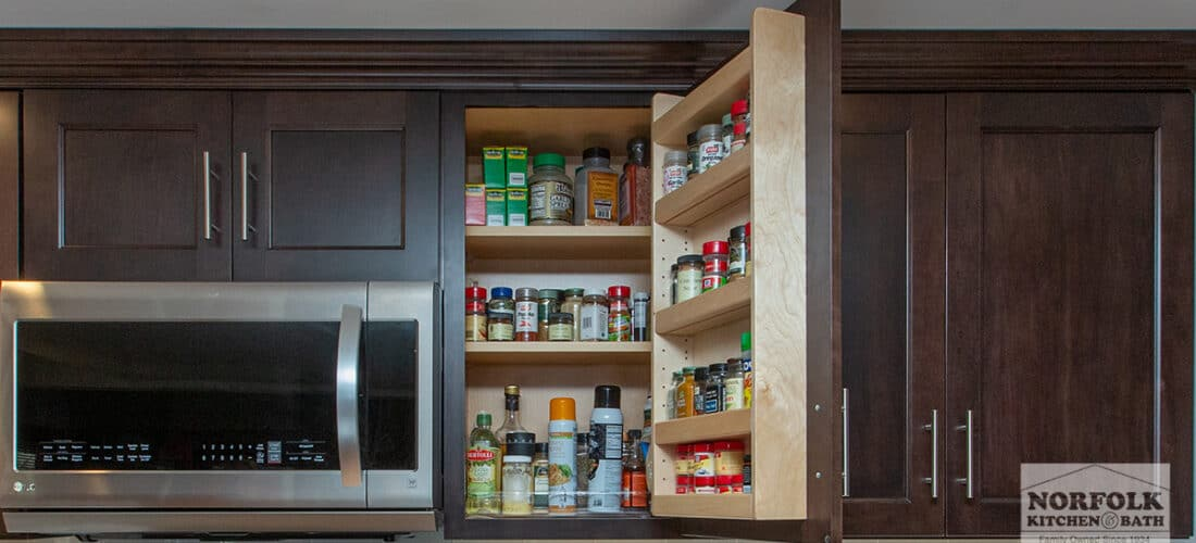 wall kitchen cabinets in a dark finish with one cabinet open to show a spice rack cabinet upgrade
