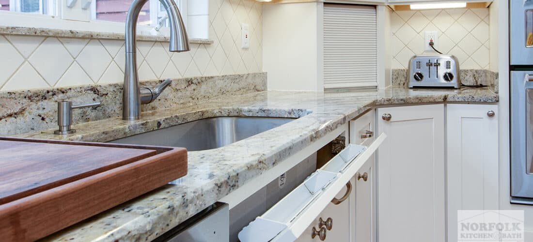 white kitchen cabinets with a granite countertop, a tilt out tray next to the kitchen sink and an appliance garage in the corner of the countertop