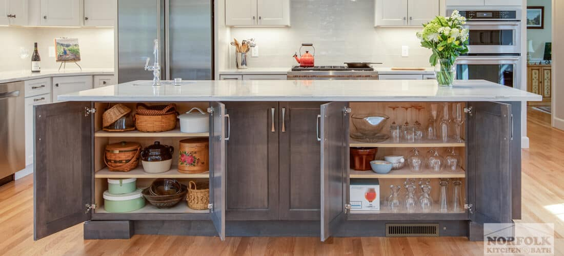 a white kitchen and a grey brown accent island with doors open to reveal storage underneath the island seating area