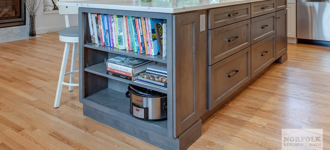 medium finish kitchen island cabinets with a built-in bookshelf on the end
