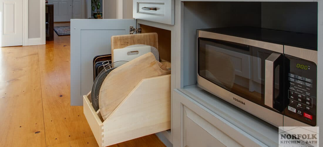 gray kitchen cabinets with a pull out tray organizer upgrade and a built in microwave cabinet