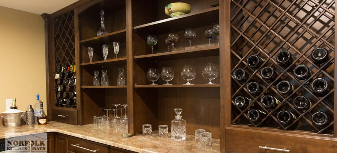 a bar area with dark finish cabinets, large wine racks on either side half filled with wine bottles and open shelving in the middle with glasses on each shelf