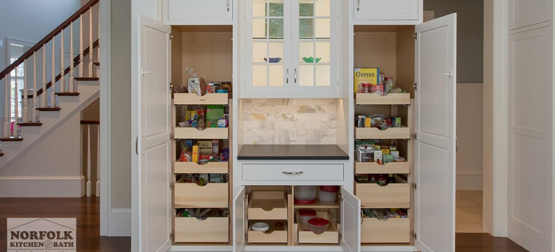 a large pantry area with 2 tall white cabinets, and a smaller double door white cabinet in the middle, all open to reveal pull out drawers with food in them