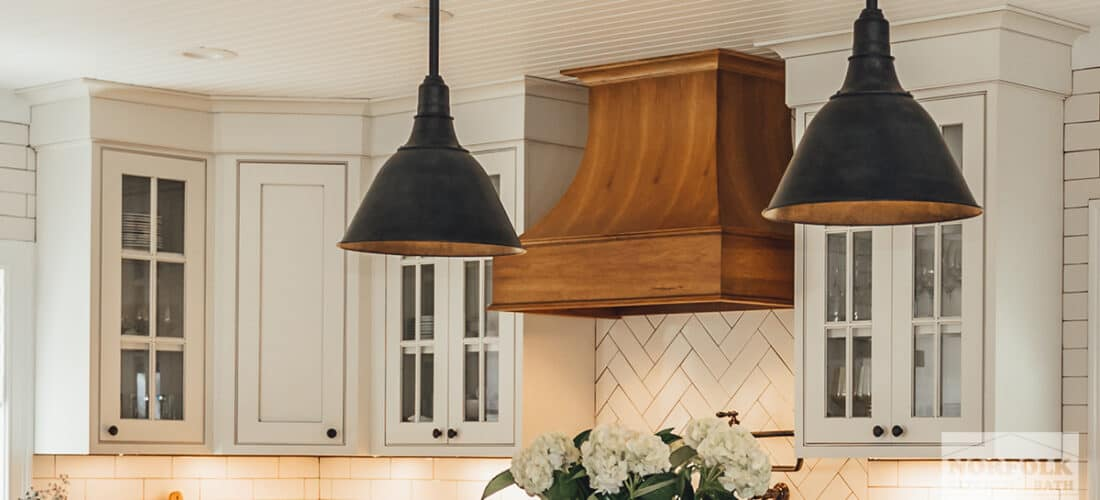 white kitchen cabinets with mullion glass doors and a decorative wood range hood in a medium hickory finish with 2 hanging pendants in front