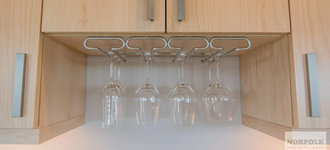 natural finish kitchen cabinets with a hanging wine glass cabinet upgrade with several wine glasses hanging from it
