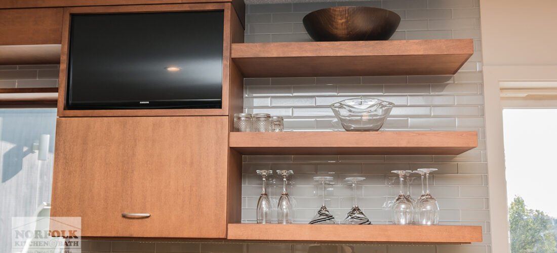 floating kitchen shelves in a medium finish with glassware on it and and a built in tv-cabinet with a small tv