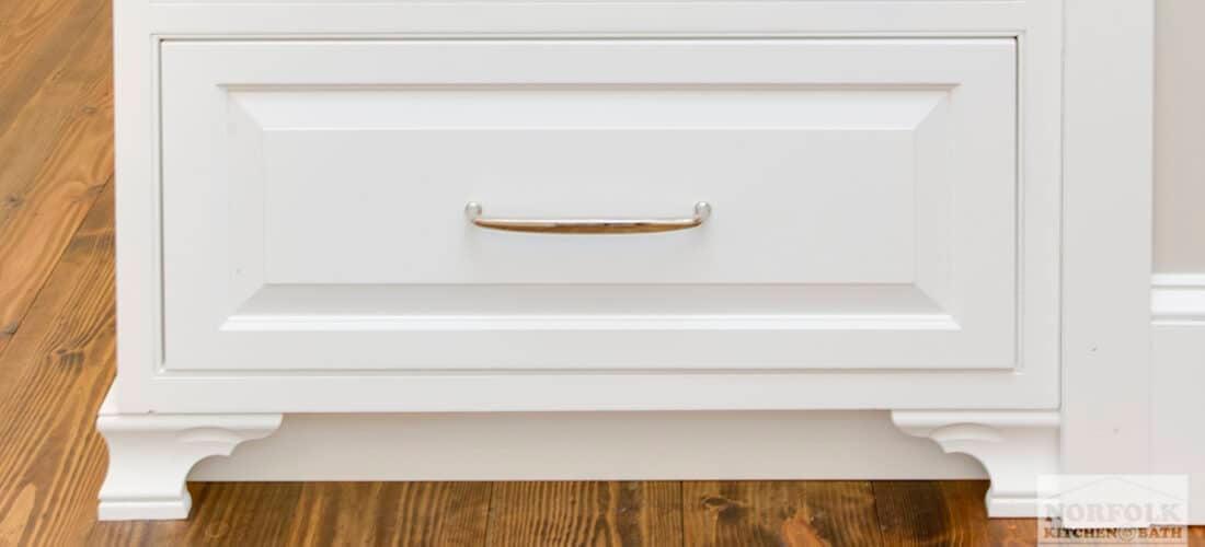 a white base kitchen cabinet with decorative base molding