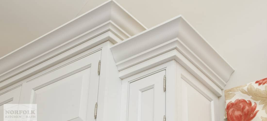 white kitchen cabinets with decorative crown molding on top