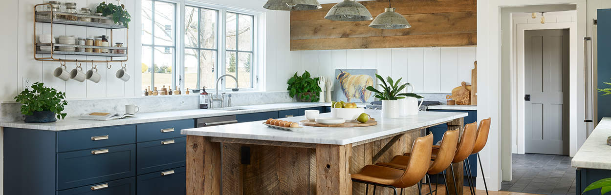 blue kitchen cabinets in a U-shaped kitchen with a rustic wood accent island in the middle