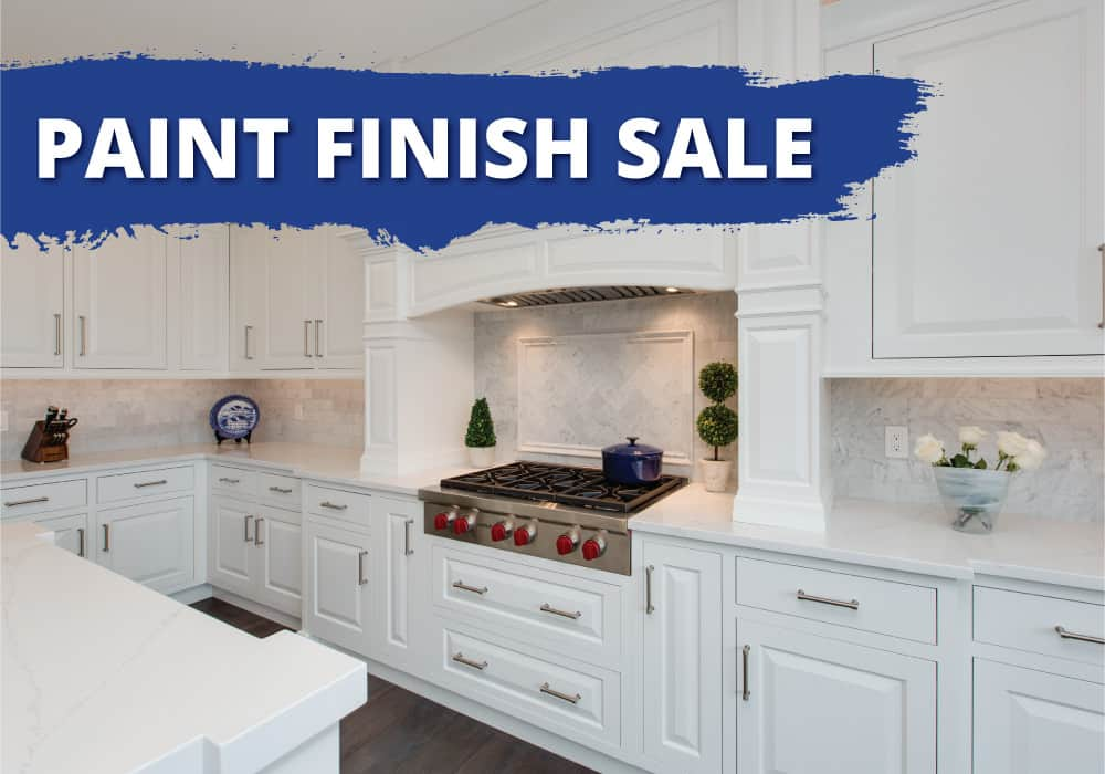 A white kitchen with a large custom wood hood with words that say