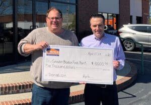 Ben Rosen from Norfolk Kitchen & Bath giving a $5,000 donation to Dave from the Greater Boston Food Bank