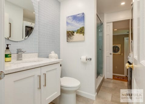 full bath remodel in Quincy, MA with floating white vanity and shower with custom folding glass door